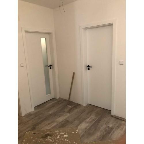 Bílé dveře s černou klikou