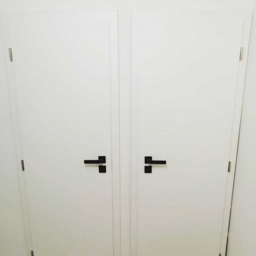 Otočné plné hladké dveře s černým kováním